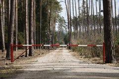 Una barriera su un sentiero nel bosco con gli alberi ed il cielo immagine stock