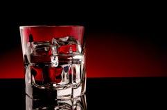 Una bebida en un vidrio con un backgro rojo Imágenes de archivo libres de regalías