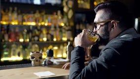 Una bebida para el hombre Primer cosechado de un whisky de consumición del hombre en la barra almacen de video