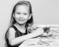 Una bella bambina con capelli biondi lunghi che si siedono ad una tavola Immagini Stock