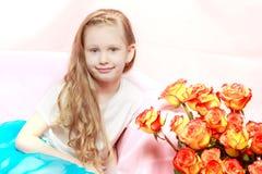 Una bella bambina con lungamente, luce, capelli ricci, in un blu Immagini Stock