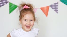 Una bella bambina dolce sta sorridendo, godente, si diverte ed esaminante la macchina fotografica Ritratto di una fine felice del archivi video