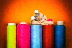 Una bella bambina ha posto la sua testa sulle bobine con il filo per cucire fotografie stock libere da diritti