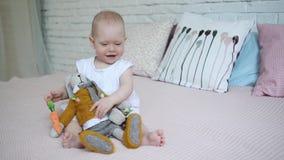 Una bella bambina sta giocando con un coniglio molle del giocattolo sul letto stock footage