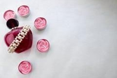Una bella bottiglia trasparente di vetro rosa di profumo femminile ha ornato con le perle grige bianche e le candele rosa della p fotografia stock