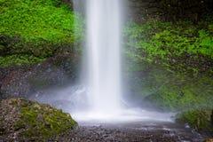 Una bella cascata che spruzza in uno stagno sotto le rocce coperte in muschio e vegetazione verdi fertili fotografie stock libere da diritti