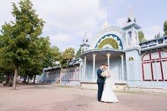 Una bella coppia delle persone appena sposate sta abbracciando contro lo sfondo della costruzione d'annata della galleria di most fotografia stock