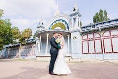 Una bella coppia delle persone appena sposate sta abbracciando contro lo sfondo della costruzione d'annata della galleria di most immagini stock libere da diritti