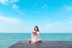 Una bella donna asiatica felice sul vestito bianco che si siede al terrazzo di legno ed al succo bevente della noce di cocco con  Fotografie Stock