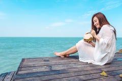 Una bella donna asiatica felice sul vestito bianco che si siede al terrazzo di legno ed al succo bevente della noce di cocco con  Immagini Stock