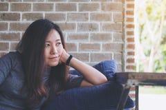 Una bella donna asiatica si siede con il mento che riposa sulle sue mani sopra un cuscino blu con ritenere felice e si rilassa in Fotografia Stock