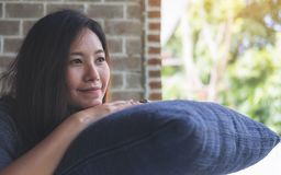 Una bella donna asiatica si siede con il mento che riposa sulle sue mani sopra un cuscino blu con ritenere felice e si rilassa in Fotografia Stock Libera da Diritti