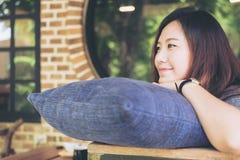 Una bella donna asiatica si siede con il mento che riposa sulle sue mani sopra un cuscino blu con ritenere felice e si rilassa in Immagini Stock