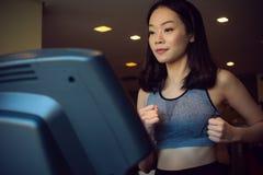 Una bella donna asiatica sta correndo fotografie stock libere da diritti