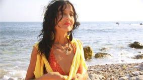Una bella donna, castana, si siede sulla spiaggia un giorno e gli orologi di estate soleggiato se sta aspettando qualcuno archivi video