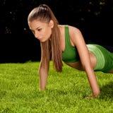 Una bella donna che fa allungando esercizio contro la natura Backg Fotografie Stock Libere da Diritti