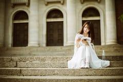 Una bella donna che si siede su una scala che legge un libro Fotografia Stock