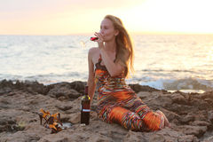 Una bella donna che si siede sulla spiaggia e sul vino bevente Fotografia Stock Libera da Diritti