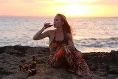 Una bella donna che si siede sulla spiaggia e sul vino bevente Immagini Stock Libere da Diritti
