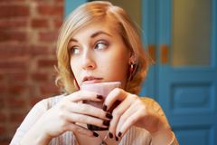 Una bella donna con brevi capelli biondi e occhi azzurri guarda fuori la finestra fotografia stock libera da diritti