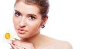 Una bella donna con il narciso fiorisce in sua mano Una ragazza con pelle sana fotografia stock