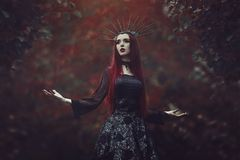 Una bella donna con pelle pallida e capelli rossi lunghi in un vestito nero e nel crownk nero Strega della ragazza con il vampiro immagine stock libera da diritti