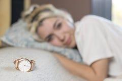 Una bella donna contenta felice che si trova a letto sorridendo alla macchina fotografica immagine stock
