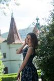 Una bella donna, una principessa in un vestito, dalla fontana in un giardino di fioritura Un castello antico nei precedenti immagini stock libere da diritti