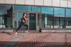 Una bella donna, una ragazza funziona di estate in città, su un trotto di mattina, pelle abbronzata Le ghette degli abiti sportiv fotografia stock
