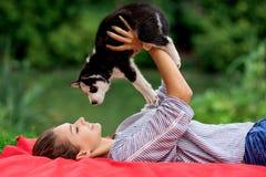 Una bella donna sorridente con una coda di cavallo e portare una camicia a strisce sta giocando con un cucciolo dolce del husky m fotografia stock