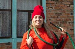 Una bella donna sorridente dell'agricoltore che posa nel suo giardino che tiene un tubo flessibile, un'agricoltura e un'imprendit Fotografia Stock