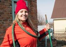 Una bella donna sorridente dell'agricoltore che posa nel suo giardino che tiene un tubo flessibile, un'agricoltura e un'imprendit Fotografie Stock Libere da Diritti