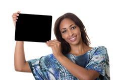 Una bella donna sostiene un calcolatore del ridurre in pani. Fotografie Stock Libere da Diritti