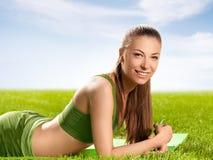 Una bella donna sportiva che fa allungando esercizio contro il natu Fotografie Stock