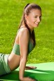 Una bella donna sportiva che fa allungando esercizio contro il natu Immagine Stock