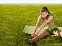 Una bella donna sportiva che fa allungando esercizio contro il natu Immagine Stock Libera da Diritti