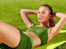 Una bella donna sportiva che fa allungando esercizio contro il natu Fotografia Stock