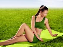 Una bella donna sportiva che fa allungando esercizio contro il natu Fotografia Stock Libera da Diritti