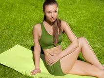 Una bella donna sportiva che fa allungando esercizio contro il natur Fotografie Stock