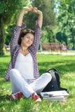 Una bella donna sta sedendosi sull'erba Fotografie Stock