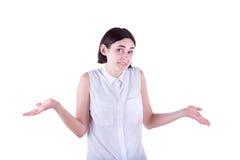 Una bella e ragazza adulta spande fuori le sue mani nel malinteso e scrolla le spalle le spalle, isolate sui precedenti bianchi Immagine Stock Libera da Diritti