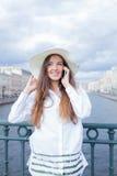 Una bella e ragazza sorridente in un cappello bianco con l'ampio bordo sta stando sul ponte e sta parlando sul telefono contro il Fotografia Stock Libera da Diritti
