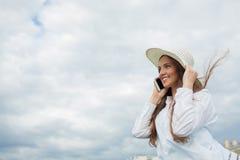 Una bella e ragazza sorridente in un cappello bianco con l'ampio bordo sta stando sul ponte e sta parlando sul telefono contro il Fotografie Stock Libere da Diritti