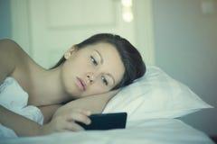 Una bella femmina si trova a letto e non può cadere addormentato e non legge le notizie sullo smartphone insonnia psicologia Immagini Stock