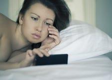 Una bella femmina si trova a letto e non può cadere addormentato e non legge le notizie sullo smartphone insonnia psicologia phob Immagine Stock Libera da Diritti