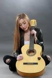 Una bella giovane bionda con una chitarra classica Immagini Stock