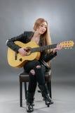 Una bella giovane bionda con una chitarra classica Fotografie Stock Libere da Diritti