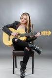 Una bella giovane bionda con una chitarra classica Immagine Stock