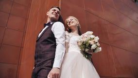 Una bella giovane coppia sta vicino alla parete marrone di un edificio alto Gli amanti sorridono archivi video