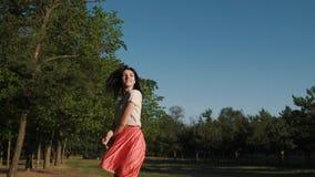 Una bella giovane donna è allegramente camminante e saltante nel legno video d archivio